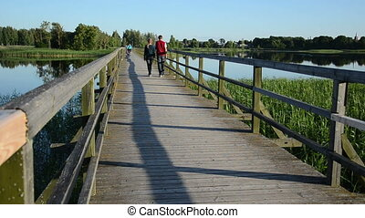 couple walk bridge lake