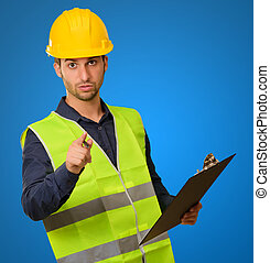 Young Engineer Holding Writing Pad Gesturing On Blue...