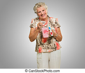 Senior Woman Holding 3d Glasses And Popcorn On Grey...