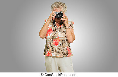 Senior Woman Capturing Photo Isolated On Grey Background