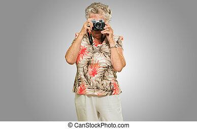 Senior Woman Capturing Photo Isolated On Grey Background