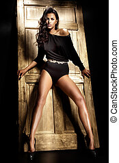 Beautiful brunette with long tanned legs looking at camera -...
