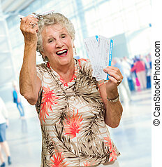 Senior Woman Holding Boarding Pass And Miniature, Indoors