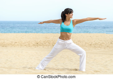 Woman exercising pilates and yoga on beach - Young brunette...