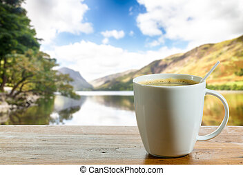 Cup of coffee on wooden table by lake