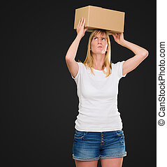 woman holding a box on her head against a black background