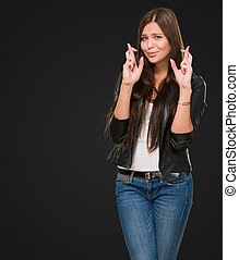 Young Woman With Crossed Fingers against a black background