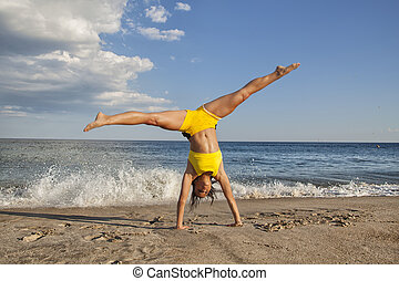 cartwheel - woman doing cartwheel on the beach fit female