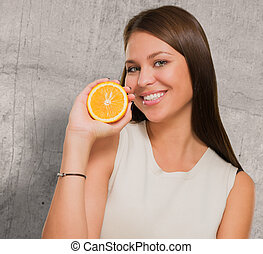 Portrait Of A Young Woman Holding Orange
