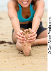 Foot and stretching concept on beach - Female hands grabbing...