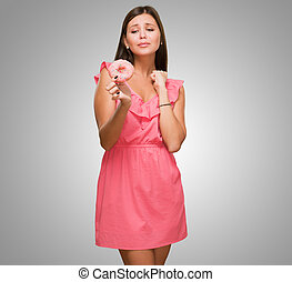 Young Woman Tempted To Eat A Donut against a grey background
