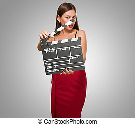 Woman In A Red Dress Holding Clapper Board against a grey...