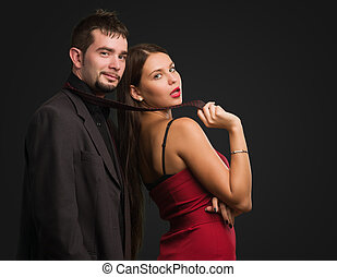 Beautiful Woman Holding Businessman Tie against a black...
