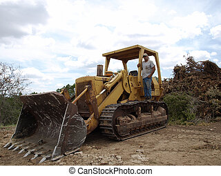 A man and his bull dozer - Bulldozer operator standing on...