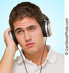 Young Man Listening to Music With Headphones against a blue...
