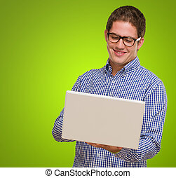 Happy Young Man Using Laptop against a green background