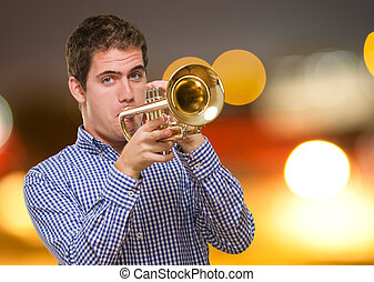 Young Man Blowing Trumpet against a city by night