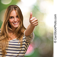 Young Woman Showing Thumb Up Sign against a nature...