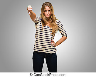 Young Woman Showing Thumb Down Sign against a grey...
