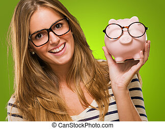 Woman Holding Piggy bank Wearing Glasses against a green...