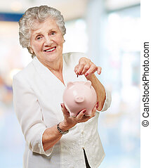 Portrait Of A Mature Woman With A Piggy Bank