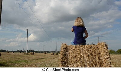 woman straw bale - young blond girl teen sit on straw bale...