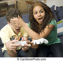 Teens play videogames on couch - A girl holds her hand over...