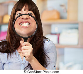 Woman Holding Magnifying Glass On Mouth, Indoor