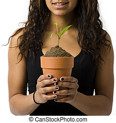 Girl with potted plant smiles - A girl with a potted plant...