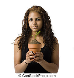 Girl holds potted plat - A girl holds a potted plant