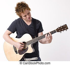 Boy plays acoustic guitar - A boy plays acoustic guitar