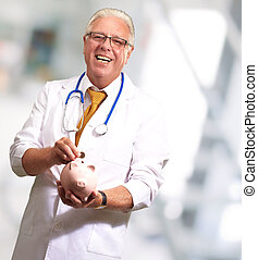 Male Doctor Putting Coins In A Piggy Bank, Indoor