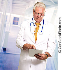 Senior Doctor Using Digital Tablet, Indoors