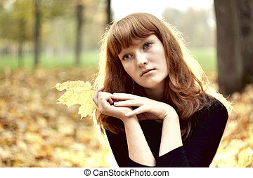 Beautiful redhaired girl sitting alone