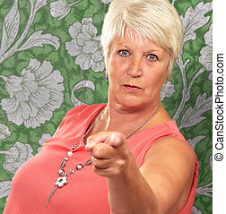 Portrait Of A Senior Woman Pointing Finger On A Wallpaper