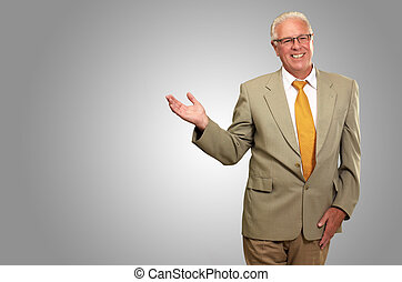 Senior Business Man Presenting Isolated On gray Background