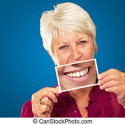 Senior Woman With Manifying Glass Showing Teeth On Blue...