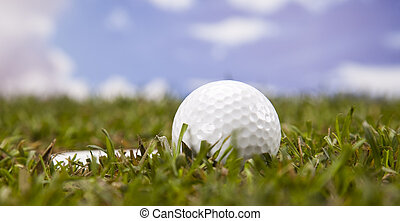 Golfball in green grass - Golf ball on green grass over a...