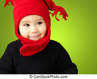 Portrait Of Baby Boy Wearing Warm Clothing against a green...
