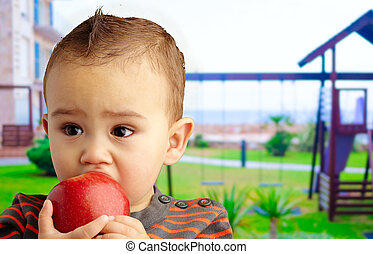 Portrait Of Baby Boy Eating Red Apple at a playground