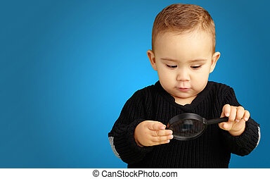 Baby Boy looking at Magnifying Glass against a blue...