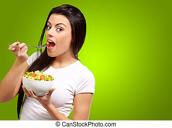 Young Girl Eating Salad From Bowl Isolated On Green...