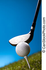 Golf ball on tee in driver - Golf ball on green grass over a...