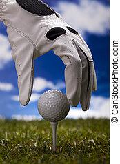 Golf ball in human hand - Golf ball on green grass over a...