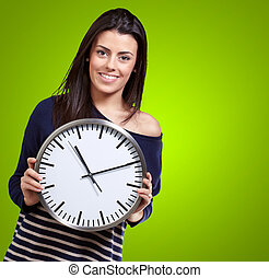 Young Girl Showing Clock On Green Background