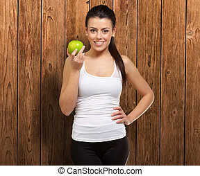 Young woman holding an apple, indoor