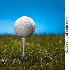 Golf ball on tee - Golf ball on green grass over a blue...
