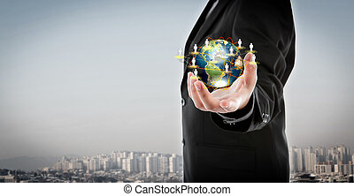 Business man holding the small world in his hands against...