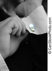 Checking the cufflink. - A groom checks the cufflinks.