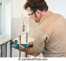 Electrician Using Grinder - Electrician using a grinder to...
